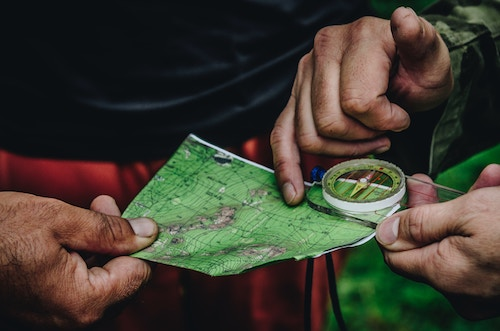 campers holding a compass on a green trail map